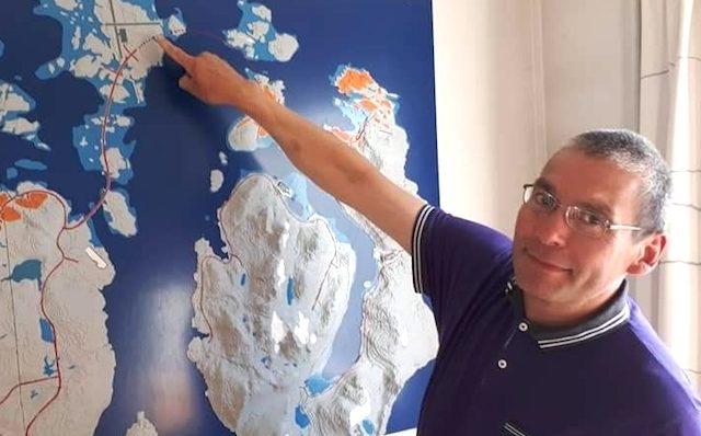 Christian Jerimiassen peger på den foreslåede alternative placering af lufthavnen i Nuuk på øen Angisunnguaq. Nuuk ses på kortet over hans albue. (Foto fra Facebook)