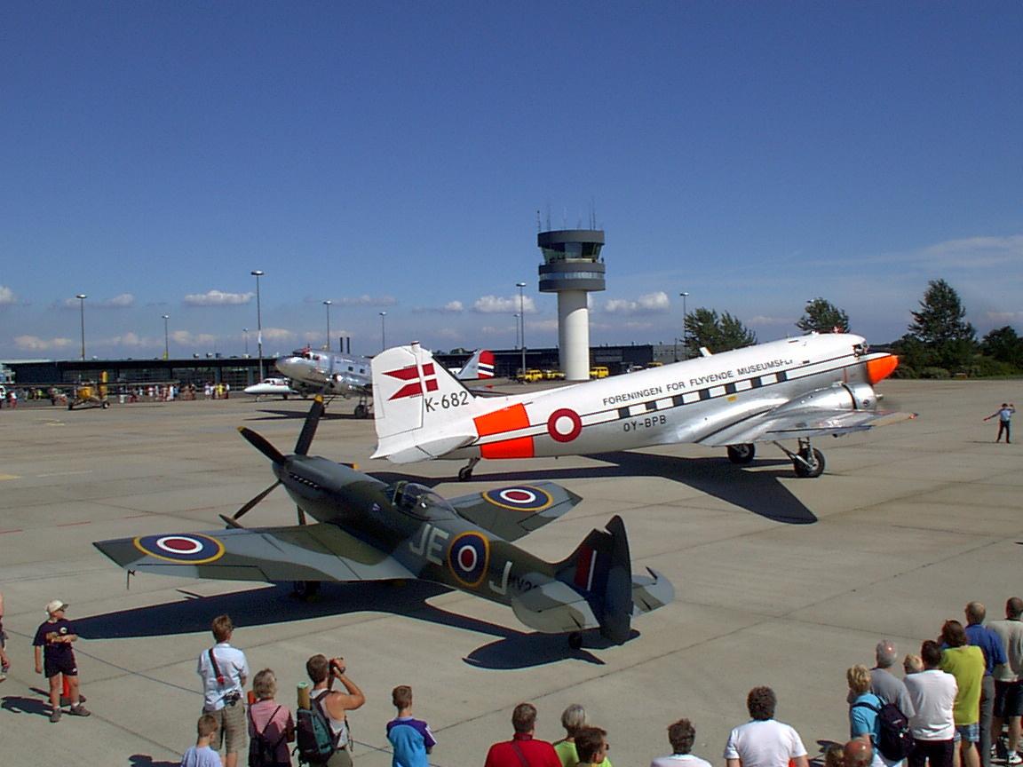 DC-3'eren fra Foreningen for Flyvende Musesumsfly, OY-BPB, holder her foran kontroltårnet i Roskilde Lufthavn. I forgrunden er en Spitfire. Foto: Jørgen, Creative Commons 3.0