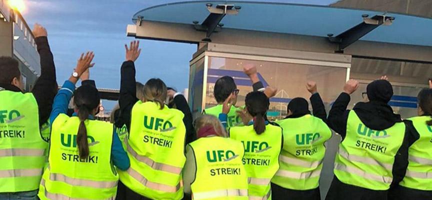 En række medlemmer af den tyske fagforening UFO rækker armene i vejret i forbindelse med deres strejke. Foto: UFO
